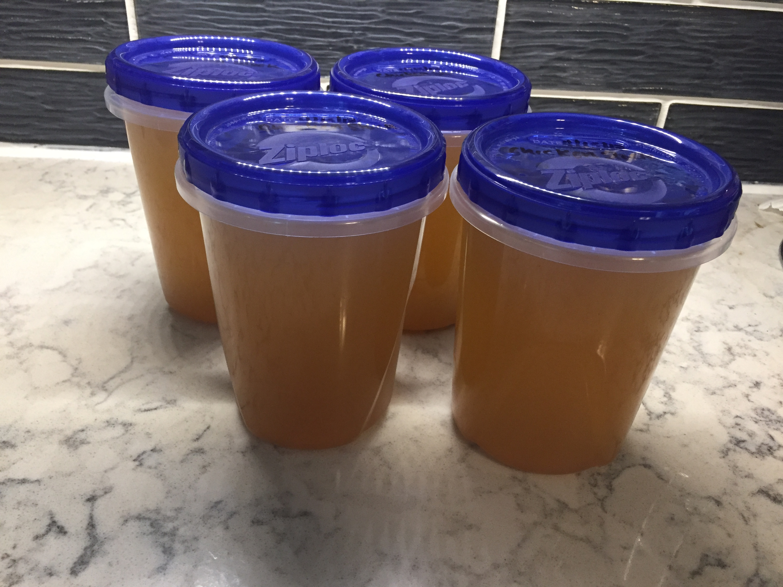 Four freezer containers of chicken broth
